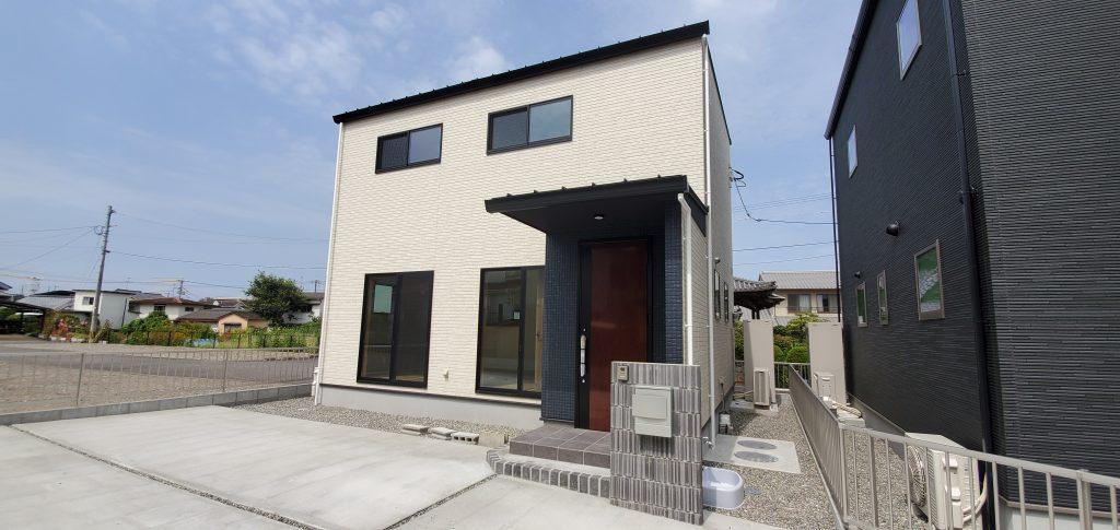 大分市津守西棟のSAKAIの新築建売 白い外観で、玄関周辺の黒い外壁とこげ茶の玄関ドアがアクセントになっている