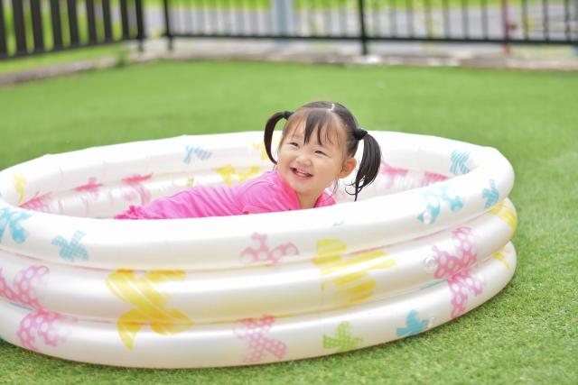 一戸建ての庭でプールを楽しむ子ども