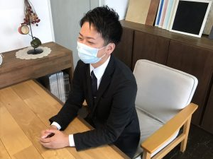 大分不動産情報サービス テーブルでインタビューを受けている山口の写真