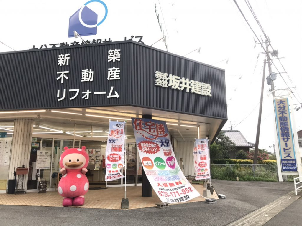 SAKAI株式会社戸次店の外観と玄関前にいるOBSのマスコットキャラクターまるんちゃん