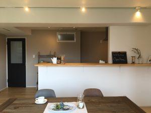 ライティングレールがキッチンカウンター上部に通っているリビングの写真